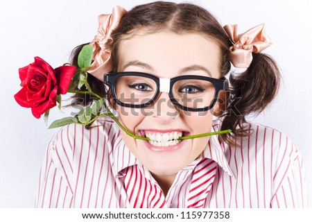 Portrait Of Geeky Young Woman Wearing Nerd Glasses Holding Rose In His Mouth In A Depiction Of Valentines Day Love - stock photo