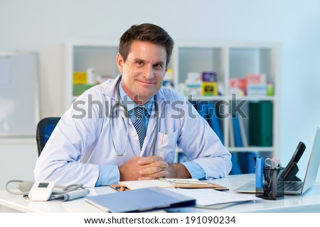 Portrait of general practitioner sitting at the table in his office
