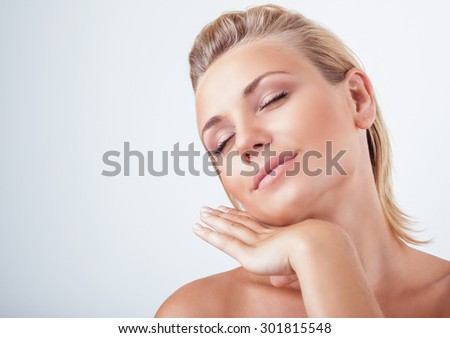Portrait of gentle calm girl with closed eyes and hand near face over light background, natural skin care, perfect complexion, enjoying day spa - stock photo