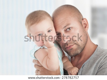 Portrait of gentle father with little daughter on hands at home, enjoying parenthood, young loving family, tenderness and love concept