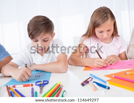 Portrait Of Girl and Boy Drawing With Colorful Markers At Home