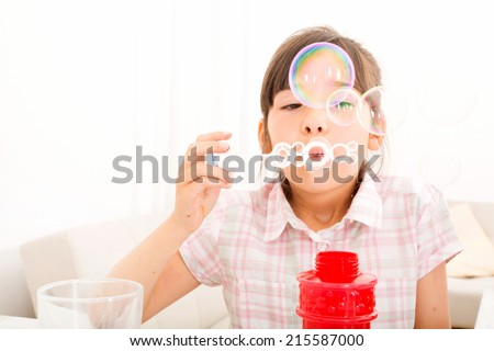 Portrait of girl blowing bubbles at home at the table.  - stock photo