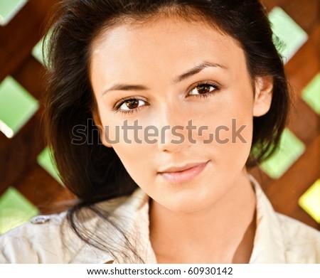 Portrait of girl close up against wooden lattice. - stock photo