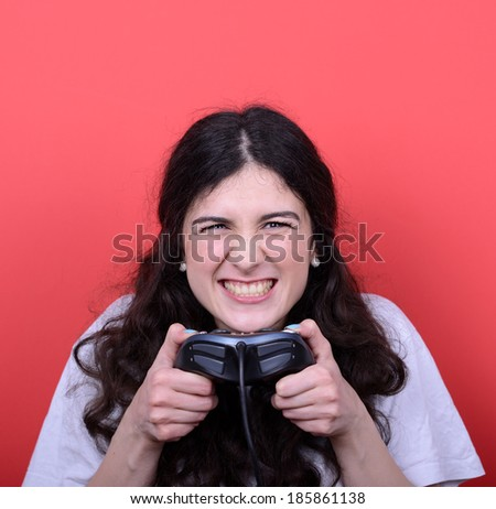 Portrait of girl holding game controller and playing games against red background - stock photo