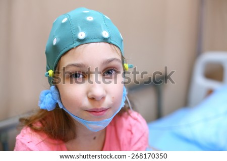 Portrait of girl in a special cap for electroencephalography in the hospital - stock photo