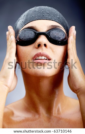 Portrait of girl in goggles and swimming cap posing before camera - stock photo