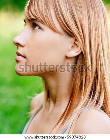 Portrait of girl in profile against green summer nature. - stock photo