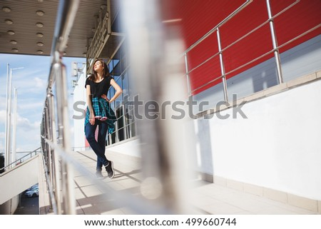 Portrait of girl in rock black style, standing outdoors in the city against the red urban wall