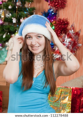 portrait of girl in Santa hat against christmas  decoration - stock photo