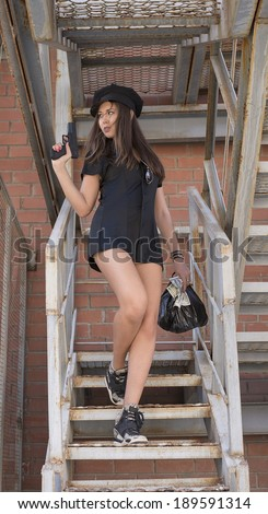 Portrait of girl in sexy uniform policewoman with gun bag full of money 100 dollar Cute woman with long slim legs holding pistol get down on stairway looking far away on red brick wall background  - stock photo