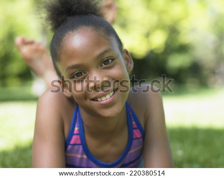 Portrait of girl laying in grass smiling - stock photo