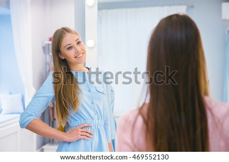 Portrait of  girl  looking at her friend in clothing department in wardrobe. Get advice.