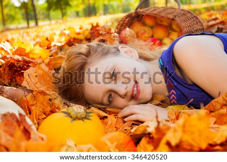 Portrait of girl on leaves with pumpkin and apples