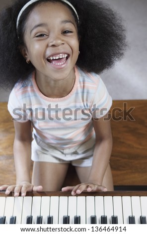 Portrait of girl playing piano - stock photo