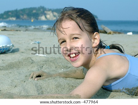 Portrait of girl playing with sand on the beach