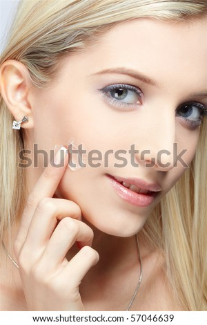 portrait of girl rubbing cream on her cheek