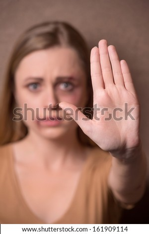 Portrait of girl showing stop to human traffic and female humiliation. Having beaten face  - stock photo