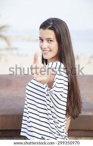 Portrait of girl showing thumb up and looking at camera. Young long-haired woman expressing positive emotions outdoors - stock photo