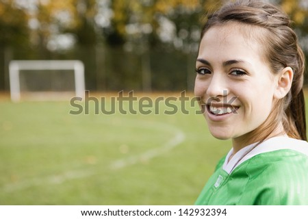 Portrait of girl smiling on soccer field - stock photo