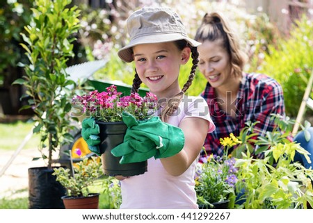 Portrait of girl standing in garden with flower pot while mother gardening in background