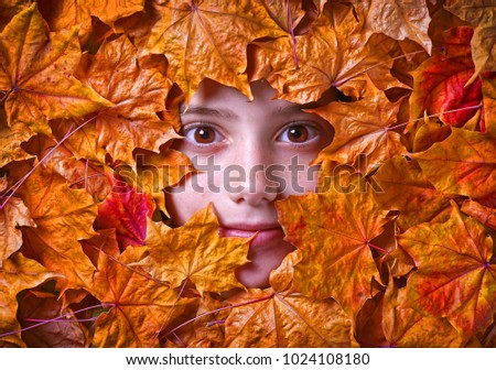 Portrait of girl surrounded with maple leaves.