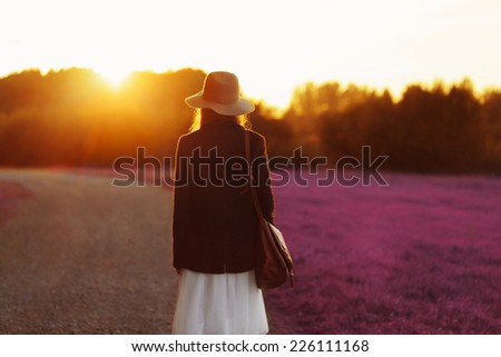 Portrait of girl walking down among the blooming fields in sunset light. Back to camera. Outside - stock photo