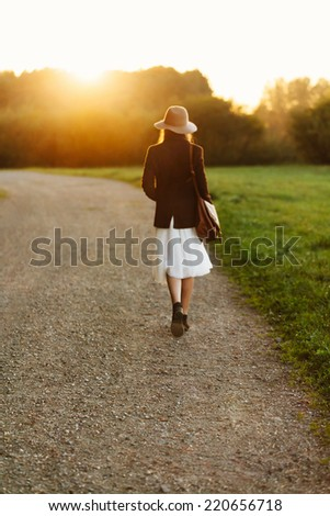 Portrait of girl walking down the countryside in sunset light. Back to camera. Outside. Focus on the road behind the girl - stock photo