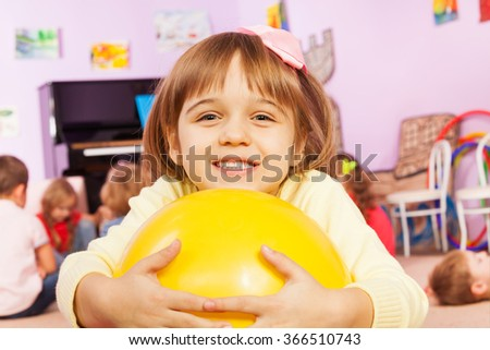 Portrait of girl with ball and friends on back