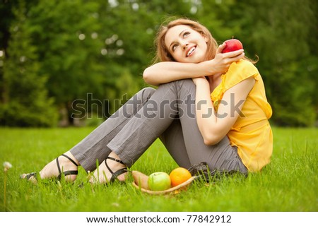 Portrait of girl with basket apples against green grass. - stock photo
