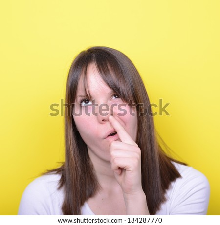 Portrait of girl with finger in her nose - stock photo
