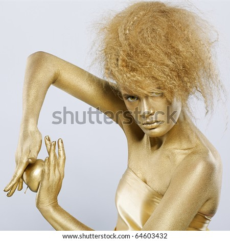 portrait of girl with golden bodyart posing with golden apple in her hands on gray