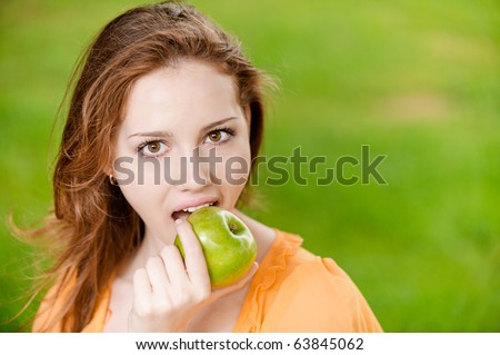 Portrait of girl with green apple against green grass. - stock photo