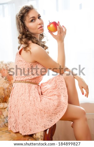 Portrait of girl with red apple. A beautiful girl eating apple.