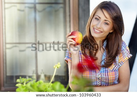 Portrait of girl with red apple against green garden.