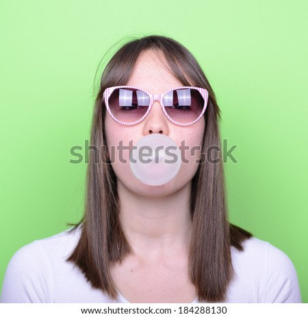 Portrait of girl with retro glasses making balloon with bubble gum against green background - stock photo
