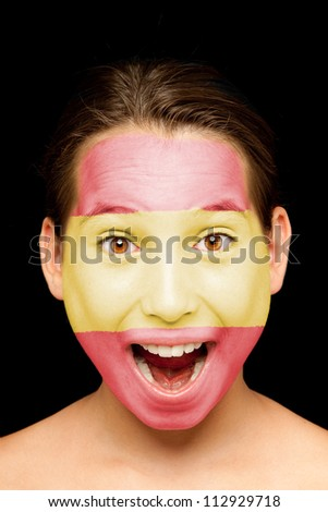 portrait of girl with spanish flag painted on her face - stock photo