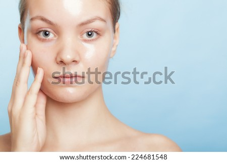 Portrait of girl young woman in facial peel off mask on blue. Peeling. Beauty and body skin care. Studio shot. - stock photo