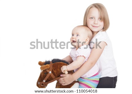 Portrait of 2 girls  riding a toy horse, isolated on white. - stock photo