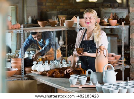 Portrait of glad  efficient woman pottery worker with ceramic crockery in hands in studio
