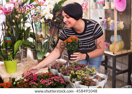 Portrait of glad female florist arranging a kalanchoe calandiva in the gardening department