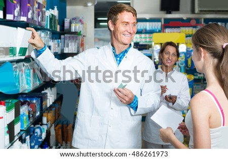 portrait of glad man druggist in white coat giving advice to customers in pharmacy