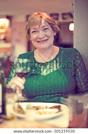 Portrait of glad retiree woman sitting in cafe and enjoying glass of wine