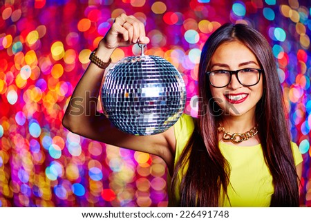 Portrait of glamorous Asian girl with sparkling disco ball looking at camera - stock photo