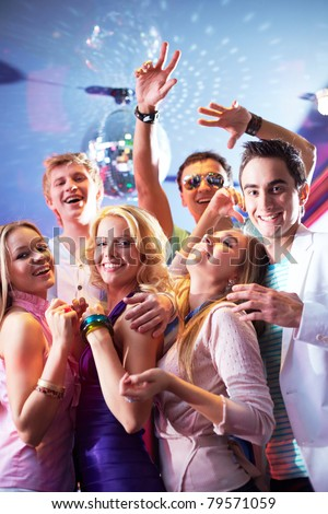 Portrait of glamorous friends dancing at party in club