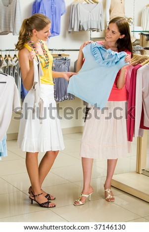Portrait of glamorous girls holding tanktops in hands while choosing new clothes in the trade center