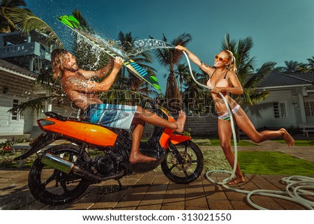 Portrait of glamorous young couple having fun with garden hose splashing summer rain on scooter  - stock photo