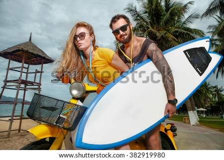 Portrait of glamorous young couple having fun with surf board on scooter   - stock photo