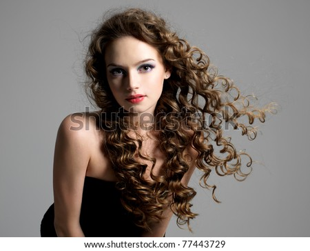 Portrait of glamour beautiful young woman with long curly hair