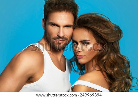 Portrait of glamour couple isolated on blue background. Attractive man and woman - stock photo