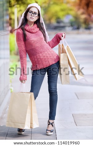 Portrait of glamour girl carrying shopping bag and dressed for winter time with hat on her head.